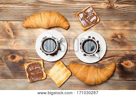 Two cups of coffee croissant toast and chocolate on wooden table