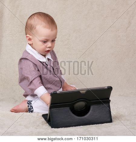 Caucasian baby boy busy using an electronic tablet becoming accustomed to a life surrounding him with technology.