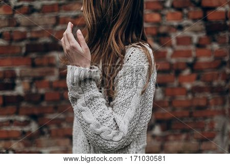 Stylish Hipster Gypsy Woman Posing In Knitted Sweater On Background Of Brick Wall, Holding Hair. Atm