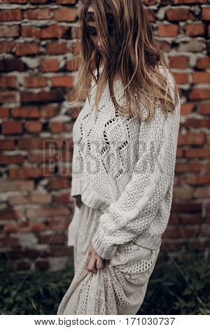 Beautiful Brunette Hipster Woman In White Boho Sweater And Dress Posing Near Old Wall