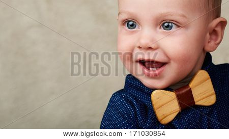 Close up of a baby boy smiling happily while wearing a blue shirt and a wooden bowtie, looking sideways into copy space