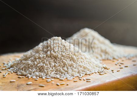 Two piles of white rice on wooden table background metaphor ingredient nutrition carbohydrate food agriculture concept selective focus