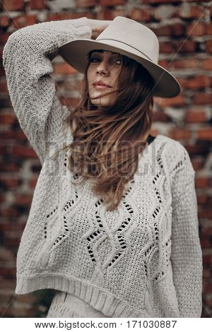 Stylish Hipster  Woman Posing In Knitted Sweater On Background Of Brick Wall, Holding Hat. Atmospher