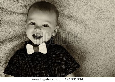 Beautiful baby boy wearing a wooden bowtie smiling at the camera in joy while lying on a soft blanket.