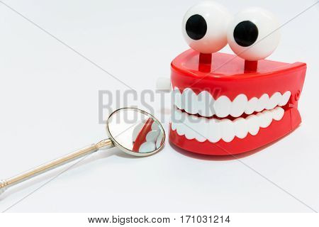 Dental care concept on white background with mirror dentist tool check up joke wind up chattering healthy teeth selective focus
