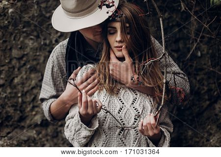Sensual Romantic Man In Cowboy Hat Hugging A Beautiful Gypsy Brunette Woman From Behind, While She I
