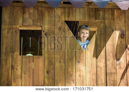 Cute Young Boy Looking Through The Window At The Playground