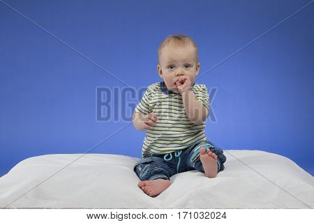 Cute little baby boy with fingers in the mouth, sitting on the white blanket, studio shot, isolated on blue background