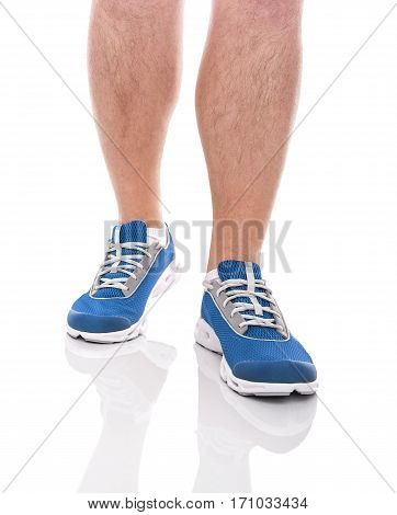 Men's sports legs in sneakers isolated on white background.