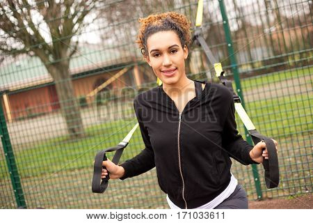 young woman exercising with a suspension trainer