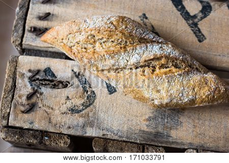 Rye whole wheat bread roll with golden crust dusted with flour on wood vintage box top view