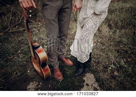 Man With Guitar Holding Hands With His Boho Gypsy Woman Closeup In Windy Field. Atmospheric Sensual