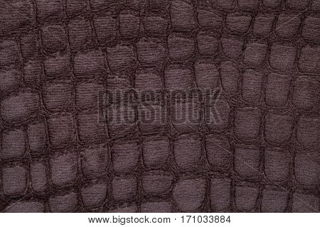 Brown background from a soft upholstery textile material closeup. Fabric with pattern imitating crocodile skin.. Textured backdrop.