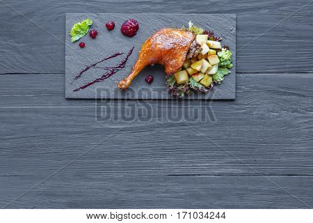 Roasted duck leg closeup served with apples and cherry sauce. Restaurant food on black slate plate, top view with copy space on wood table background