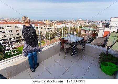 Tourist female standing on the terrace and enjoy views of the city and the Hagia Sophia in Istanbul.