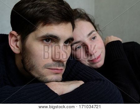 portrait of a beautiful couple in black indoor. bristly man and brunette woman.