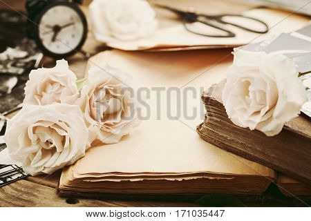 Retro still life with vintage rose flowers and open ancient book. Nostalgic composition on old wooden table.