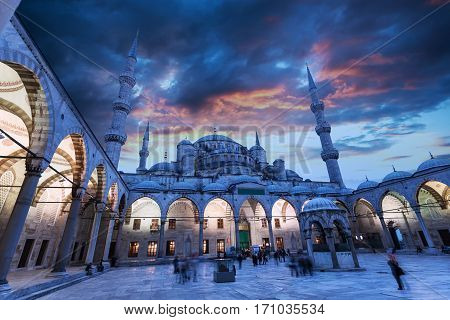 Blue Mosque or Sultanahmet Camii in Istanbul with beautiful sunset sky and with night illumination. The view from the courtyard.
