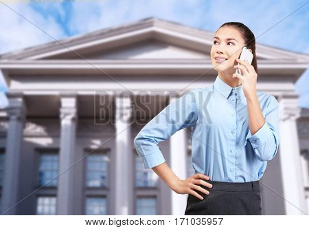 Law and justice concept. Young woman talking on phone against courthouse background