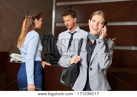 Business woman making phone call at hotel reception after check-in