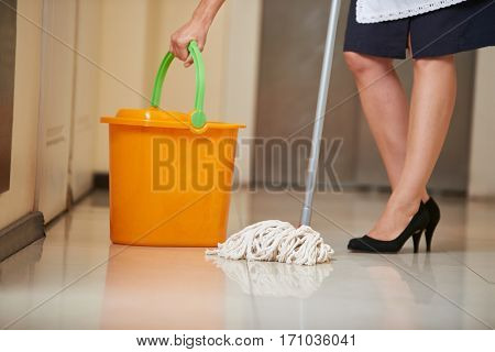 Cleaning lady with mop and bucket in a hotel
