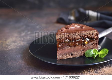 Piece Of Chocolate Sacher Torte On A Black Plate .