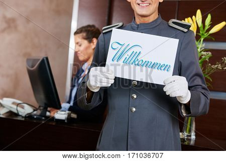 Page at hotel reception holding German sign saying