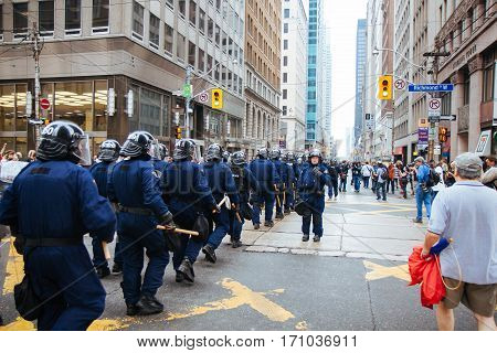 TORONTO, CANDA - JUNE 26, 2010: RCMB officers head south on Bay St. towards the convention centre to block protestors during the G20