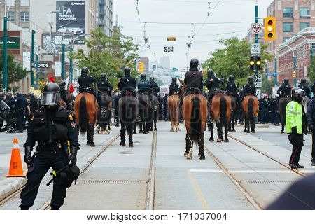 TORONTO, CANDA - JUNE 26, 2010: Police officers, mounted police and SWAT team members standoff with protestors in downtown Toronto during the G20 summit