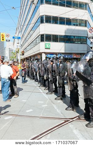 TORONTO, CANDA - JUNE 25, 2010: Police offers stand guard with shields to block the path of protestors during the G20 summit