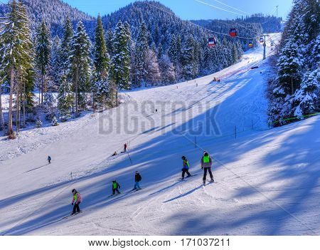 People in vacation practicing ski sport and snowboard outdoor, in Poiana Brasov - Romania
