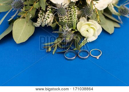 Two golden wedding rings and engagement ring with a diamond on blue background with white flowers and greenery