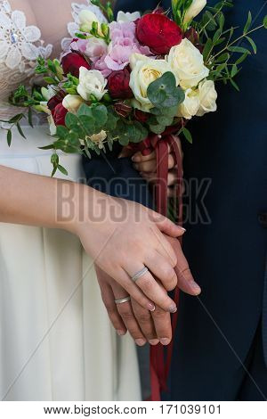 Hands of married couple with rings. Wedding bouquet with white and red roses, eucalyptus and hydrangea