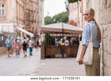 Girl with bag over shoulder walking on city street and looks back. Back view. In background are visible people.
