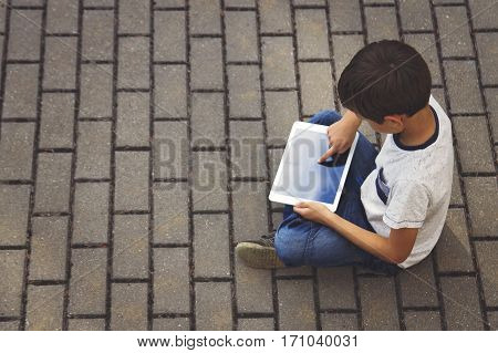 Child with tablet computer sitting on the pavement outdoors. Technology, computer addiction, education concept
