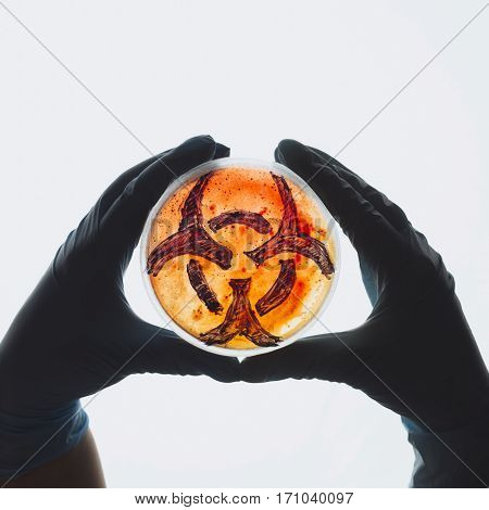 Hands hold Petri dish with biohazard symbol sign. Contaminated water food supply concept. Dangerous infectious disease. Medical lab testing research. Bacterial infection control prevention outbreak