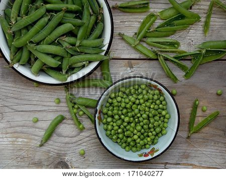 Green Pea Pods And Cleaned In A Metal Bowl On A Wooden Background