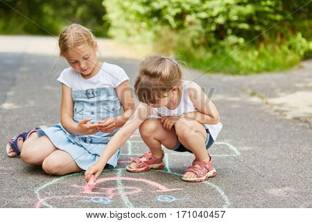 Two girls painting hopscotch with chalk on floor for fun