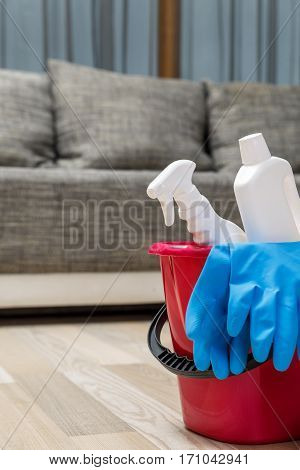 Cleaning service. Bucket with chemicals bottles and rubber gloves. Household equipment.