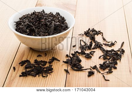 Bowls With Dry Black Tea, Scattered Leafs On Table
