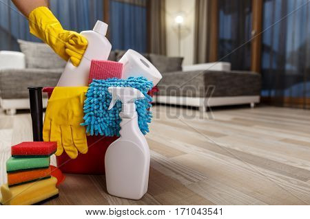 Cleaning service. Bucket with sponges, chemicals bottles and plunger. Hand in rubber glove holding a bottle. Paper towel. Household equipment.