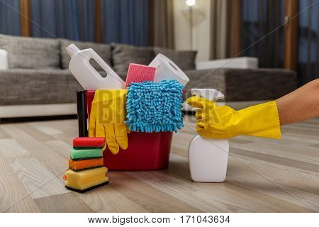 Cleaning service. Bucket with sponges, chemicals bottles and plunger. Hand in rubber glove holding a spray. Paper towel. Household equipment.