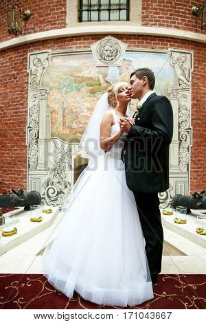 Just Married Couple Stands In A Painted Restaurant Hall
