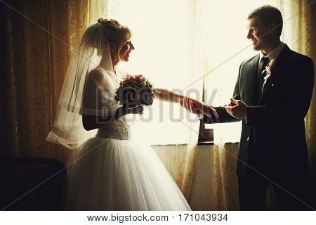 Fiance Holds Bride's Hand Tenderly Standing In The Front Of A Window