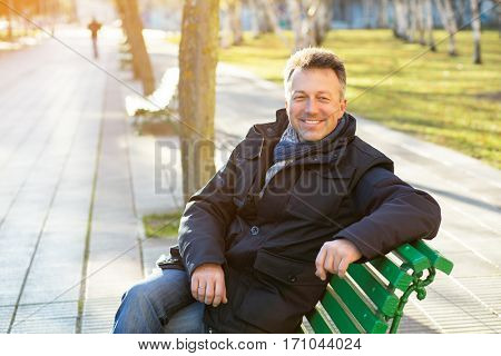 Handsome happy smiling man. Outdoor winter european male portrait. Attractive confident middle-aged man resting on bench in city park, image toned.
