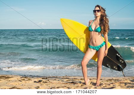 Woman holding surfboard / Portrait of surf girl over ocean background.
