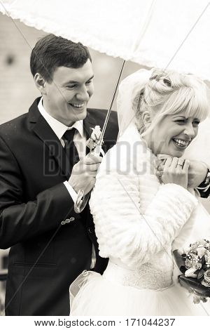 A Balck And White Picture Of A Happy Newlyweds Under An Umbrella