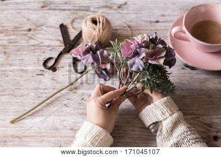 Closeup of female hands decorating with flowers selective focus