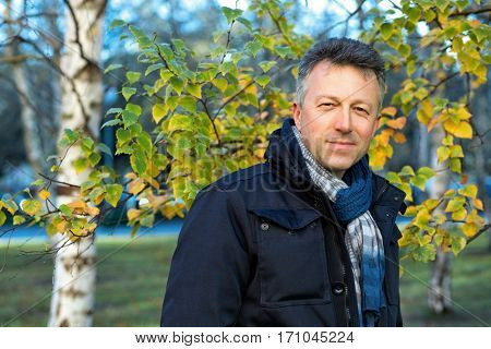 Handsome happy smiling man. Outdoor autumn male portrait. Attractive confident middle-aged man posing in city park, birch grove.