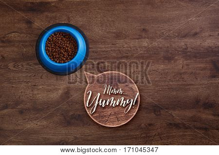 Bowl of dry kibble dog food. Mmm yummy speech bubble. Healthy pets feed. Blue plate on wooden rustic background.